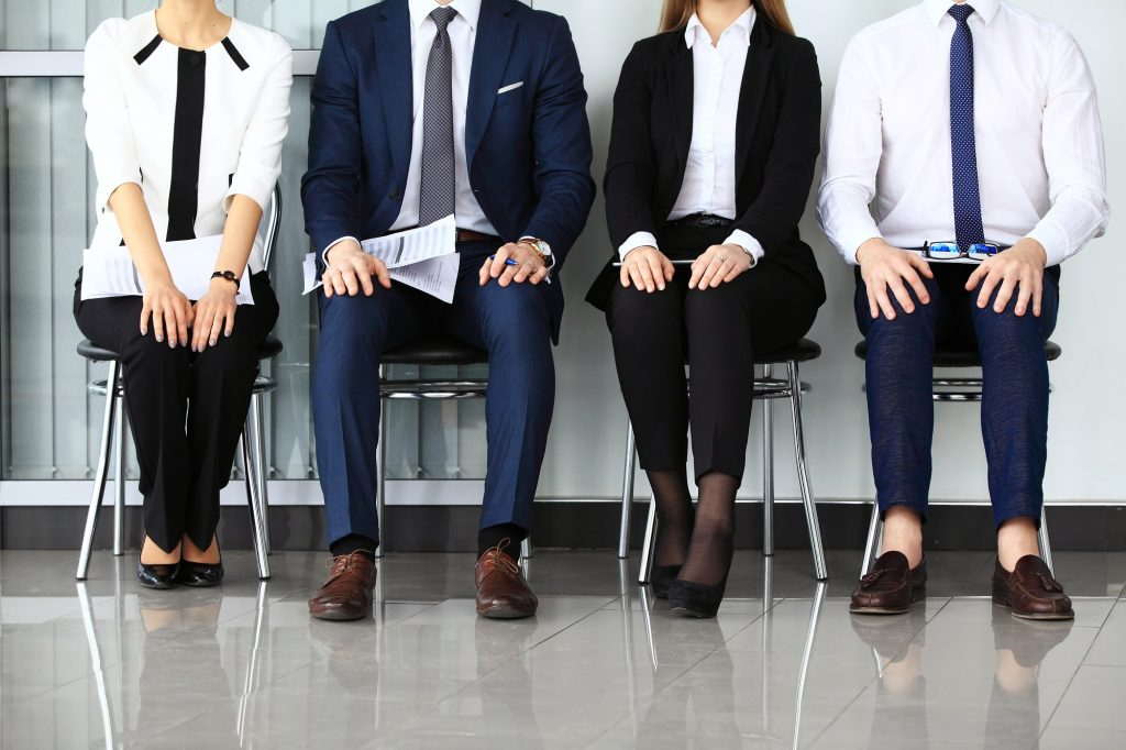 Business people waiting for job interview. Four candidates competing for one position