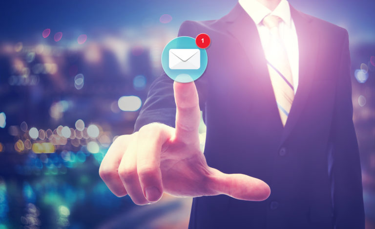 Businessman pointing at email icon on blurred city background